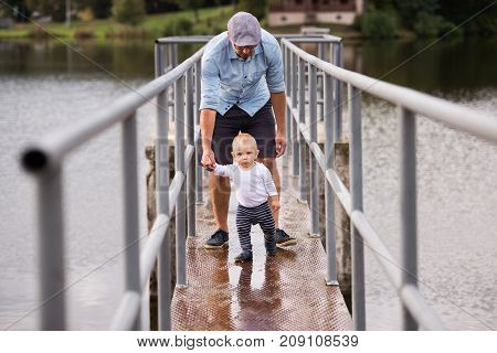 Little boy with father making first steps in nature. Summer time.