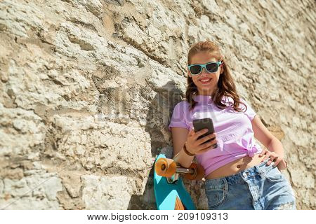 lifestyle, summer, technology and people concept - smiling young woman or teenage girl in sunglasses with longboard and smartphone over stone wall outdoors