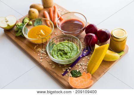 baby food, healthy eating and nutrition concept - vegetable or fruit puree in glass bowls and feeding spoon on wooden board