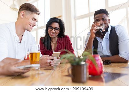 leisure, technology and people concept - group of happy international friends with smartphone drinking beer at bar