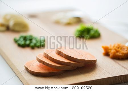food, healthy eating and nutrition concept - sliced pumpkin and other vegetables on wooden board
