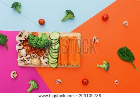 Vegetables on colorful abstract background. Healthy eating and diet. Cut raw vegetables on wooden board, copy space. Ingredients for salad or soup - mushroom, cherry tomato, broccoli, cucumber, carrot
