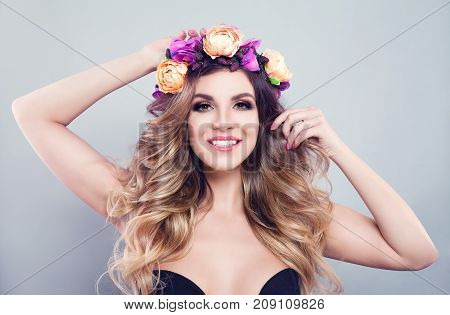 Perfect Young Woman Fashion Model with Wavy Blonde Hair Makeup and Spring Flowers Wreath on Gray Background