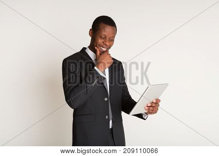 Successful, satisfied businessman in stylish suit, tie standing, holding laptop at hands. Portrait. Copy space