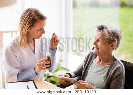 Health visitor and a senior woman with tablet during home visit. A nurse talking to an elderly woman.