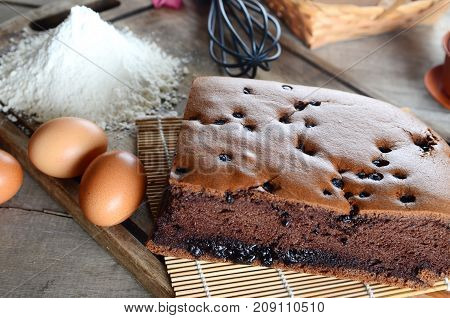 Taiwanese chocolate sponge cake with bamboo mat on wooden board
