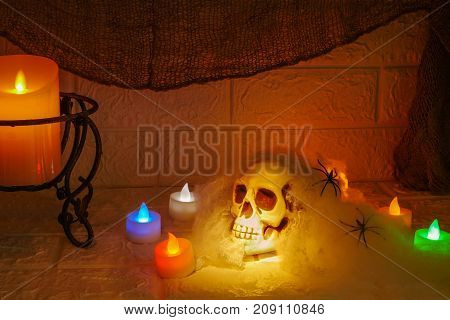 Halloween decoration colorful candles and horror skull on wall background