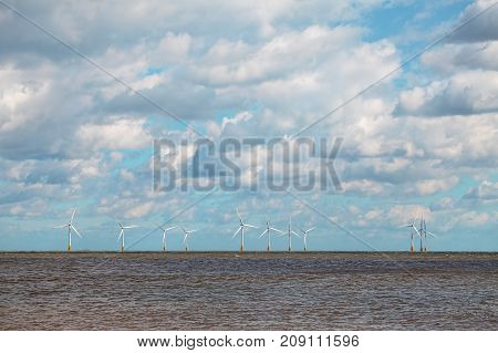 Renewable energy on the horizon. Offshore wind farm with beautiful cloudy sky. White wind turbines at sea.