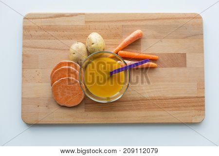 baby food, healthy eating and nutrition concept - vegetable puree or baby food in bowl with feeding spoon on wooden board