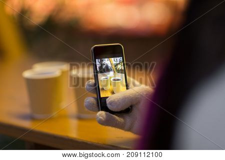 winter holidays, hot drinks and people concept - hand with mulled wine picture on smartphone at christmas market