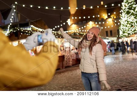 holidays, winter and people concept - happy woman posing for boyfriend with smartphone on square at christmas market
