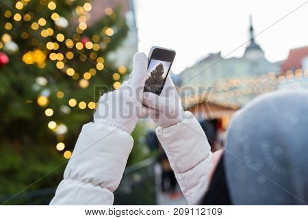 holidays, technology and people concept - hands with smartphone photographing christmas tree at old town hall square in tallinn