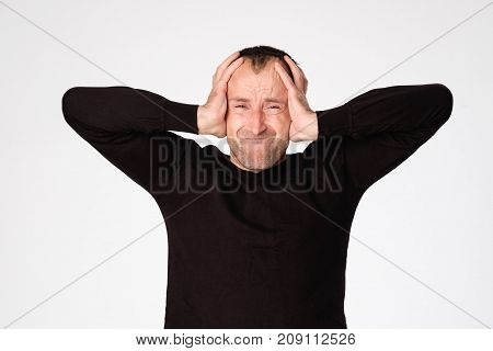 Mature spanish man closing his ears because of headache or migraine. Concept of loud sound and neurosis