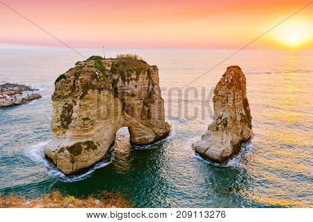 Beautiful sunset on Raouche, Pigeons' Rock. In Beirut, Lebanon.Sun and Stones are reflected in water.dense clouds in the sky.