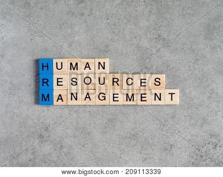 Word spell Human Resources Management on bare cement or concrete wall background