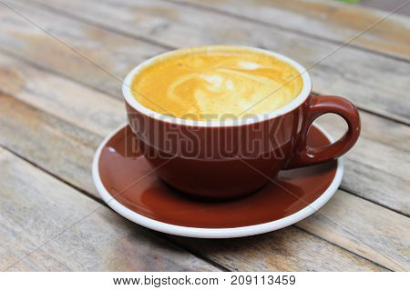 Cup of golden Latte on a wooden table