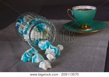 Appetizing sweet homemade blue and white marshmallows in a glass jar and a mug of tea on a canvas on a gray background.