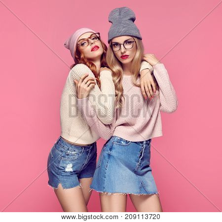 Fashion. Young Beautiful woman in Stylish Autumn outfit Hugging. Pretty Sisters Best Friends Twins. Hipster Blond Redhead Model, fashion Cozy jumper, Glasses. Girls in Trendy Beanie hat on Pink