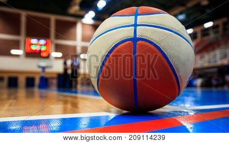 Basketball ball on court floor close up with blurred arena in the background and two defocused coaches talking on court.