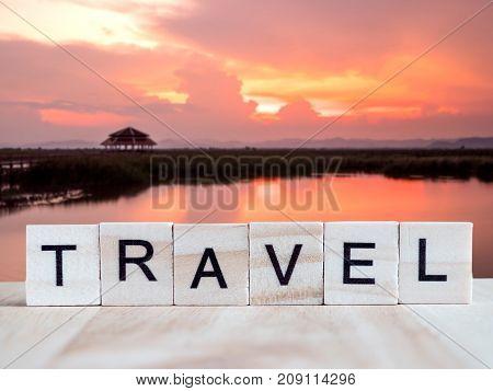 Word spell Travel by wooden tile font on blur landscape sunset background