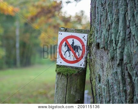 Horse riding prohibited or forbidden sign in black, white, red in forest near Berlin, Germany.