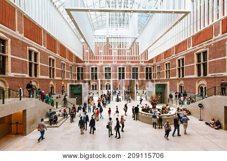 AMSTERDAM, THE NETHERLANDS - AUGUST 03, 2017: Visitors in modern main hall in the new atrium of the Rijksmuseum. Entrance to museum, massive ceiling decorations and people in dutch national museum.