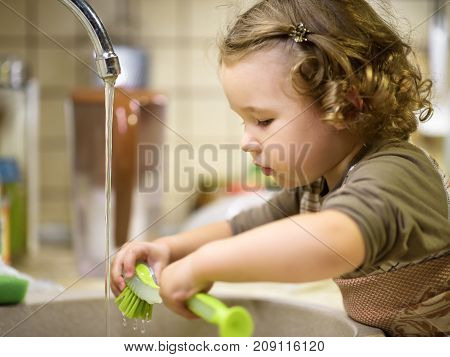 Pretty two-year girl washes the dishes in kitchen. Little child uses a brush for washing of ware.