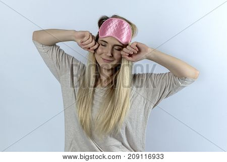 A Young Woman Or A Student In Pajamas And A Blindfold Yawns And Is Sleepy. Hands Touch The Face And