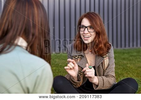 Young Woman Listens To News Gossip From Her Girlfriend Sitting On The Grass In The Park