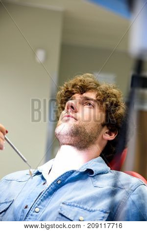 A young man waiting for the beginning of a Dental procedure.