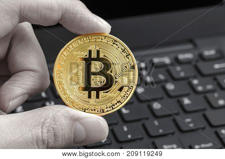 Golden bitcoin in fingers with the black and white laptop keyboard background . Crypto currency concept.