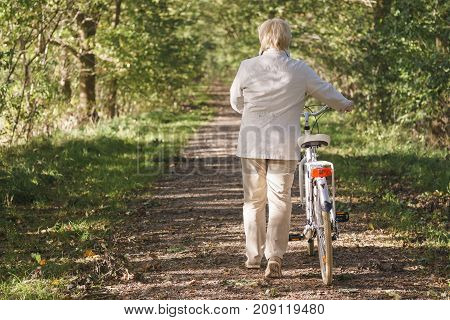 Active Happy Carefree Smiling Senior Woman Ridding Bike In Autumn Nature.