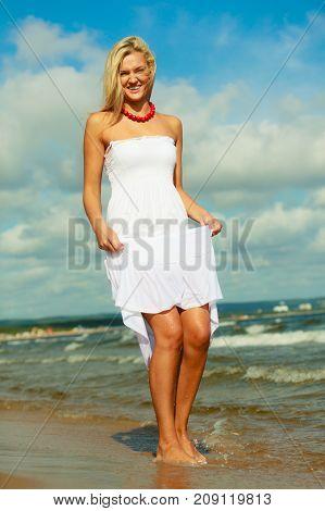 Blonde Woman Wearing Dress Walking In Water