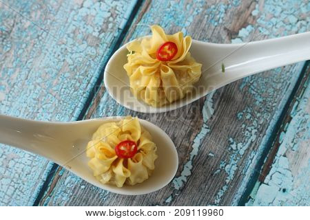 two steamed wonton on the spoon top view