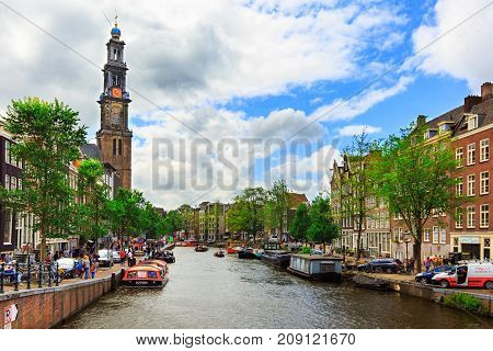 Amsterdam, Netherlands - August 3, 2017: Traditional holland houses, Westerkerk church, boats and people on Prinsengracht canal. Dutch street in summer city. Urban landscape with typical architecture.