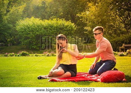 Love and dating. Young fashionable couple lovers with big red heart in park. Woman and man argument. Picnic concept.
