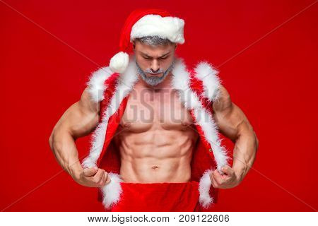 Christmas. Sport, activity. Sexy Santa Claus . Young muscular man wearing Santa Claus hat demonstrate his muscles. Isolated on red background.