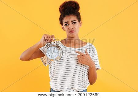 Upset african woman holding alarm clock and pointing on them over yellow background