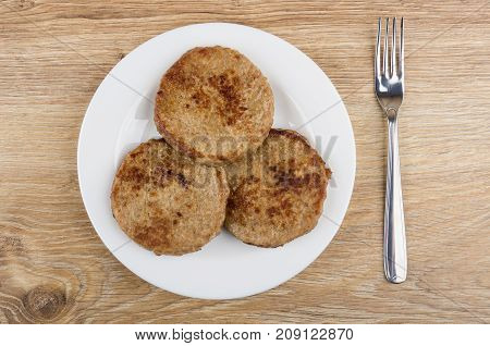 Fried Cutlets In White Plate And Fork On Wooden Table