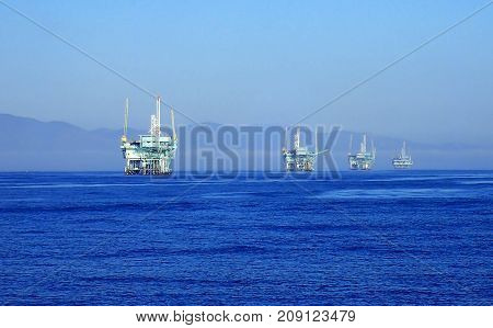 Line of Oil Rigs Sits in Ocean Off California Coast