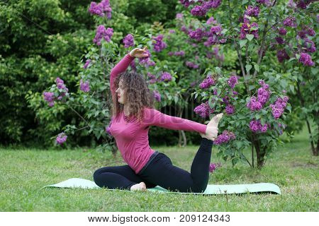 Woman practicing yoga on rug near bushes of blossoming lilacs at spring day