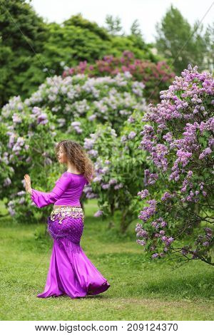 Pretty belly dancer performs in purple costume near bushes of blossoming lilacs at spring
