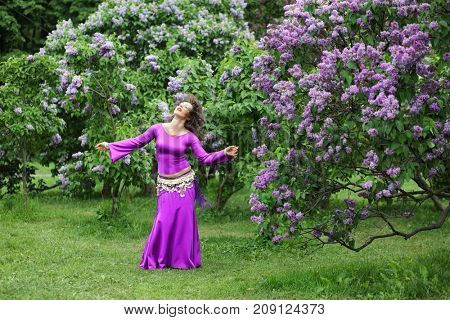 Belly dancer performs in purple costume near bushes of blossoming lilacs at spring