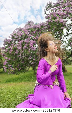 Woman in purple costume for belly dance sits on lawn near bushes of blossoming lilacs at spring