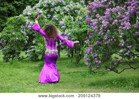 Belly dancer performs in purple costume near bushes of blossoming lilacs at spring, back view