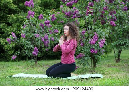 Woman practicing yoga on rug near bushes of blossoming lilacs at spring