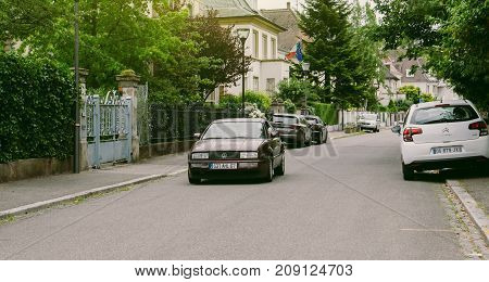 STRASBOURG FRANCE - JUN 25 2017: Vintage Volkswagen Scirocco coupe driving through an upper-class neighbourhood in Strasbourg France