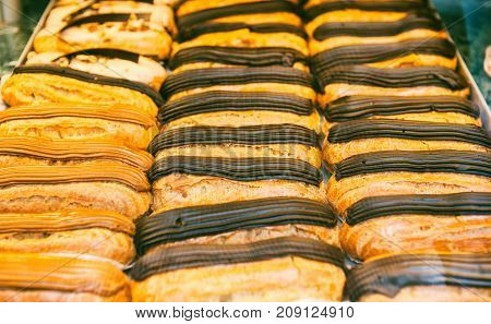 Savory coffee and chocolate eclair desserts in a French pattiserie vitrine glass display case