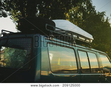 Sunflare light over the camping van with roof-mounted cargo box