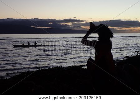 Hawaii or Polynesian Silhouette Man Blowing Traditional Trumpet Shell Welcome with Canoe Offshore